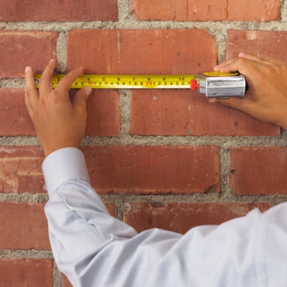 Measuring tape on brick wall
