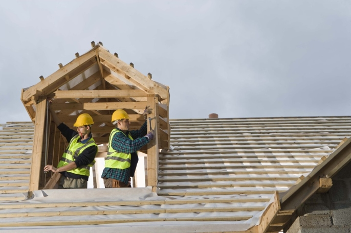 Construction workers building the roof of a house