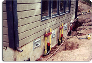 Push piers lifting (yellow) and helical piers (silver) holding back foundation.