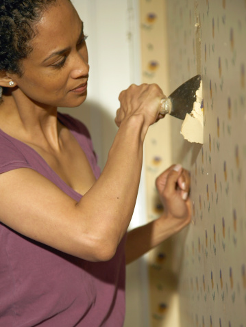 Woman scraping a wall
